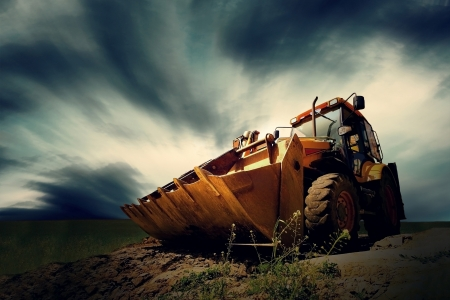 Yellow tractor on sky background photo