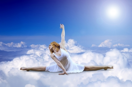 Ballerina seating on the sky clouds photo