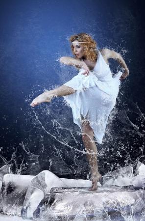 Jump of ballerina on the ice dancepool around splashes of water drops photo