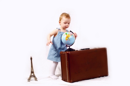 A little girl with globe and old baggage photo