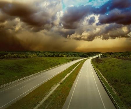 conducci�n: Bonita vista sobre el camino bajo el cielo con las nubes Foto de archivo