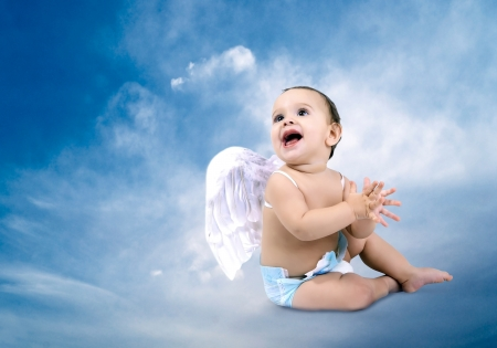 Beautiful Baby angel sitting on the clouds photo