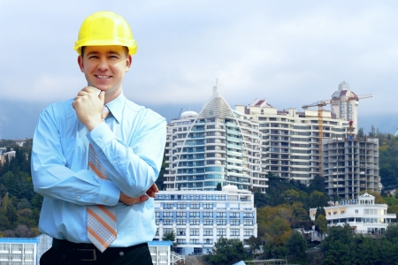Young architect wearing a protective helmet standing on the mountains building  photo