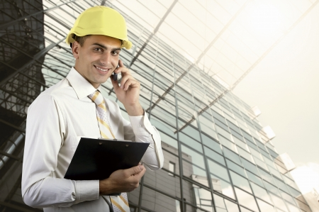 Young architect wearing a protective helmet standing on the building outdoor background Stock Photo - 22578924