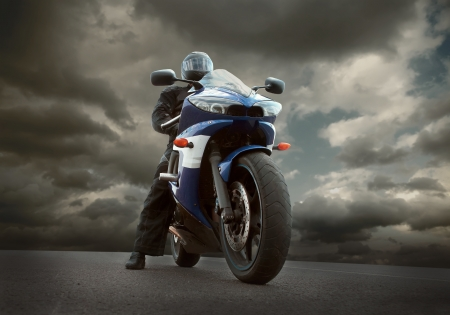 casco moto: El hombre en el asiento de la motocicleta bajo el cielo con nubes