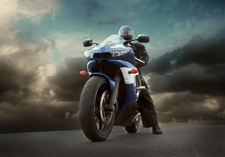 Man seat on the motorcycle under sky with clouds photo