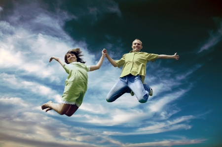 Fun couple in jump on the outdoor background photo