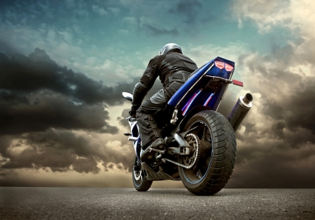 sports clothing: Man seat on the motorcycle under sky with clouds Stock Photo
