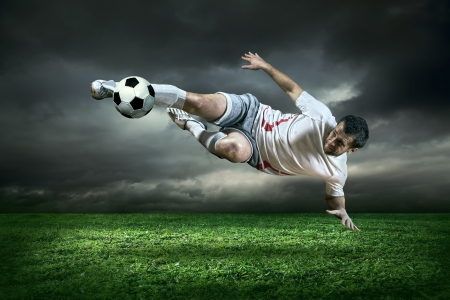 soccer grass: Football player with ball in action under rain outdoors Stock Photo