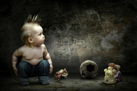Baby boy around their toys looking at the image on the grunge wall photo