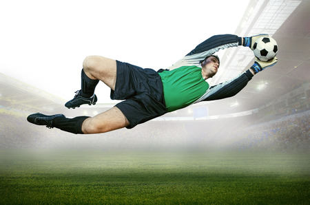 Football goalkeeper in action on field of stadium photo
