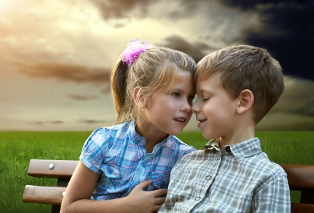 Loving brother and sister sitting outdoors photo