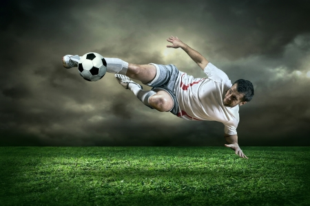 football fan: Football player with ball in action under rain outdoors Stock Photo
