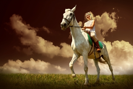 Young horsewoman riding on white horse, outdoors view Stock Photo - 25104314