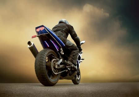 motorcycle: Man seat on the motorcycle under sky with clouds Stock Photo