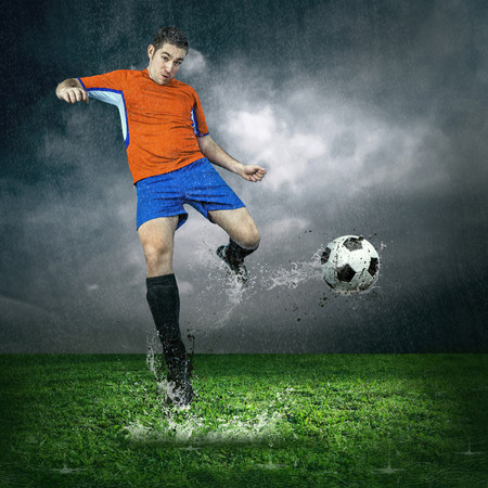 Football player with ball in action under outdoors rain photo