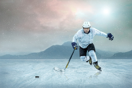 frozen lake: Ice hockey player on the ice, outdoor. Stock Photo