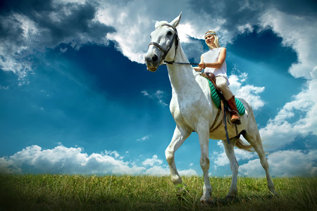 Young horsewoman riding on white horse, outdoors view Stock Photo - 26659093