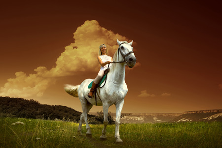 Young horsewoman riding on white horse, outdoors view Stock Photo - 26959109