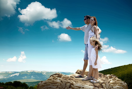 Family stay on the top of mountain, looking on the beautiful view. Stock Photo