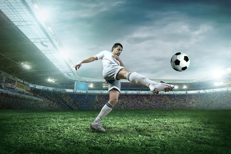 football fan: Soccer player with ball in action outdoors. Stock Photo