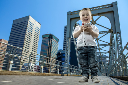 Boy with gadget on the bridge in the city of skyscrapers Stock Photo - 27486510