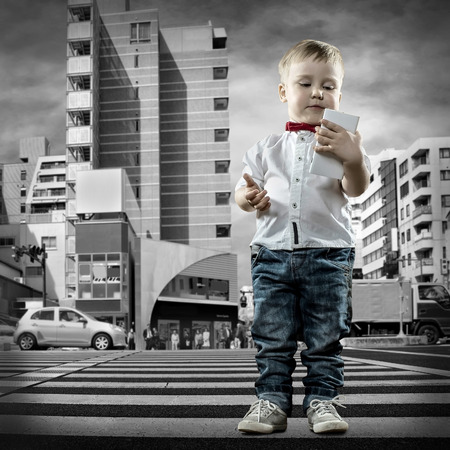 Child with phone stay on the crossroad Stock Photo - 27486511