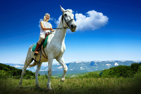 Young horsewoman riding on white horse, outdoors view