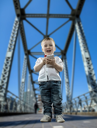 Boy with phone on the bridge in the city of skyscrapers Stock Photo - 27746013