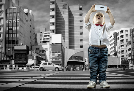 Child with phone stay on the crossroad Stock Photo - 27857349