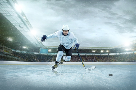 hockey goal: Ice hockey player on the ice. Open stadium - Winter Classic game.