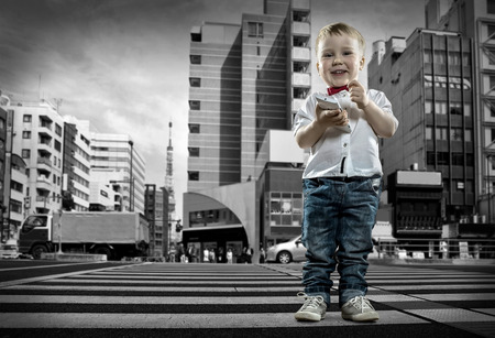 zebra crossing: Child with phone stay on the crossroad Stock Photo