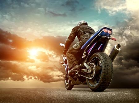 v�locit�: Man si�ge sur la moto sous le ciel avec des nuages Banque d'images