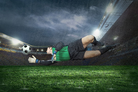 Football golkeeper with ball in action under rain in stadium Stock Photo - 30155513