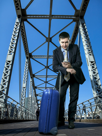 Man with baggage speaking by phone on the bridge  Stock Photo - 30202755