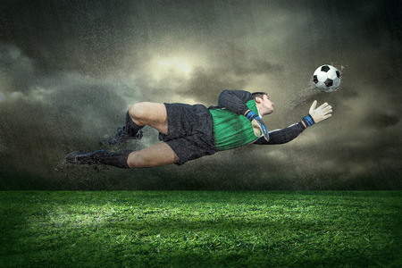 Football player with ball in action under rain outdoors Stock Photo - 30202763