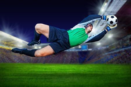 Football goalkeeper in action on field of stadium Reklamní fotografie