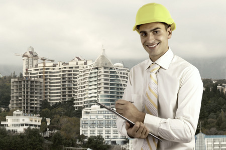 Young architect wearing a protective helmet standing on the building outdoor  photo
