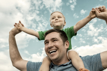 young parents: Son seating on the father under beautiful sky