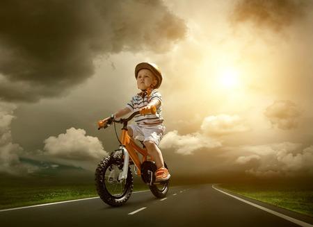 niños en bicicleta: Niño de estar en la bicicleta de color naranja y el transporte por carretera no urbano bajo el cielo