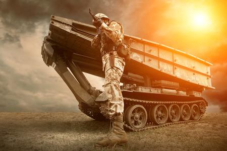 Tanque militar y soldado al aire libre. Foto de archivo