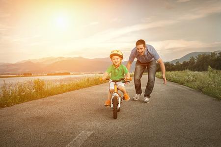 ni�os en bicicleta: Padre Felicidad e hijo en la bicicleta al aire libre Foto de archivo
