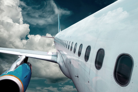 supersonic transport: Airplane at flying under sky with clouds Stock Photo