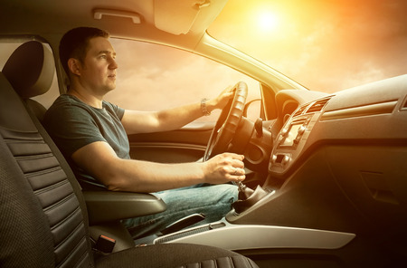 Man sitting and driving in the car under sunset sky photo