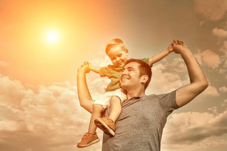 Zoon zitplaatsen op de vader onder mooie hemel met zon Stockfoto