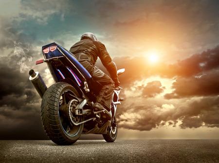 casco de moto: Asiento Hombre en la motocicleta bajo el cielo con nubes Foto de archivo