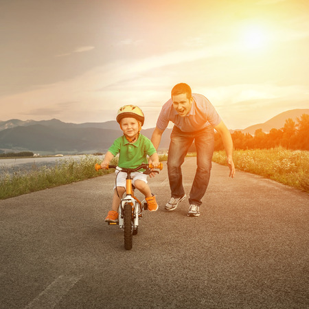 adult offspring: Happiness Father and son on the bicycle outdoor