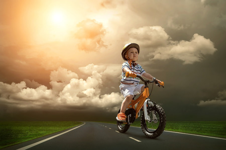 Child seating on the orange bicycle and travelling on the non-urban road under sky photo