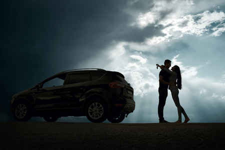 Silhouette of happiness couple stay near the new car under sky photo