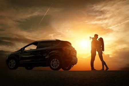 dream car: Silueta de la felicidad pareja alojarse cerca del nuevo coche bajo el cielo